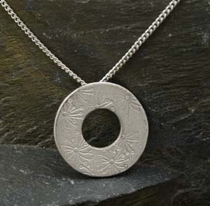 Silver round washer type pendant with stamped flower design